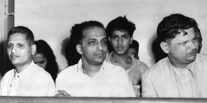 The men accused of the assassination of Mahatma Gandhi listen to testimony in a courtroom during their arraignment in New Delhi, India, on May 27, 1948.  Gandhi was shot three times by Nathuram Vinayak Godse, center, on his way to a prayer meeting from Birla House on Jan. 30.  At left is Narayan Dattraya Apte and at right is Vishnu Ramkrishna Karkare.  In second row at center is Madan Lal, accused of exploding a bomb on Jan. 20 outside a Gandhi prayer meeting at Birla House.  (AP Photo)